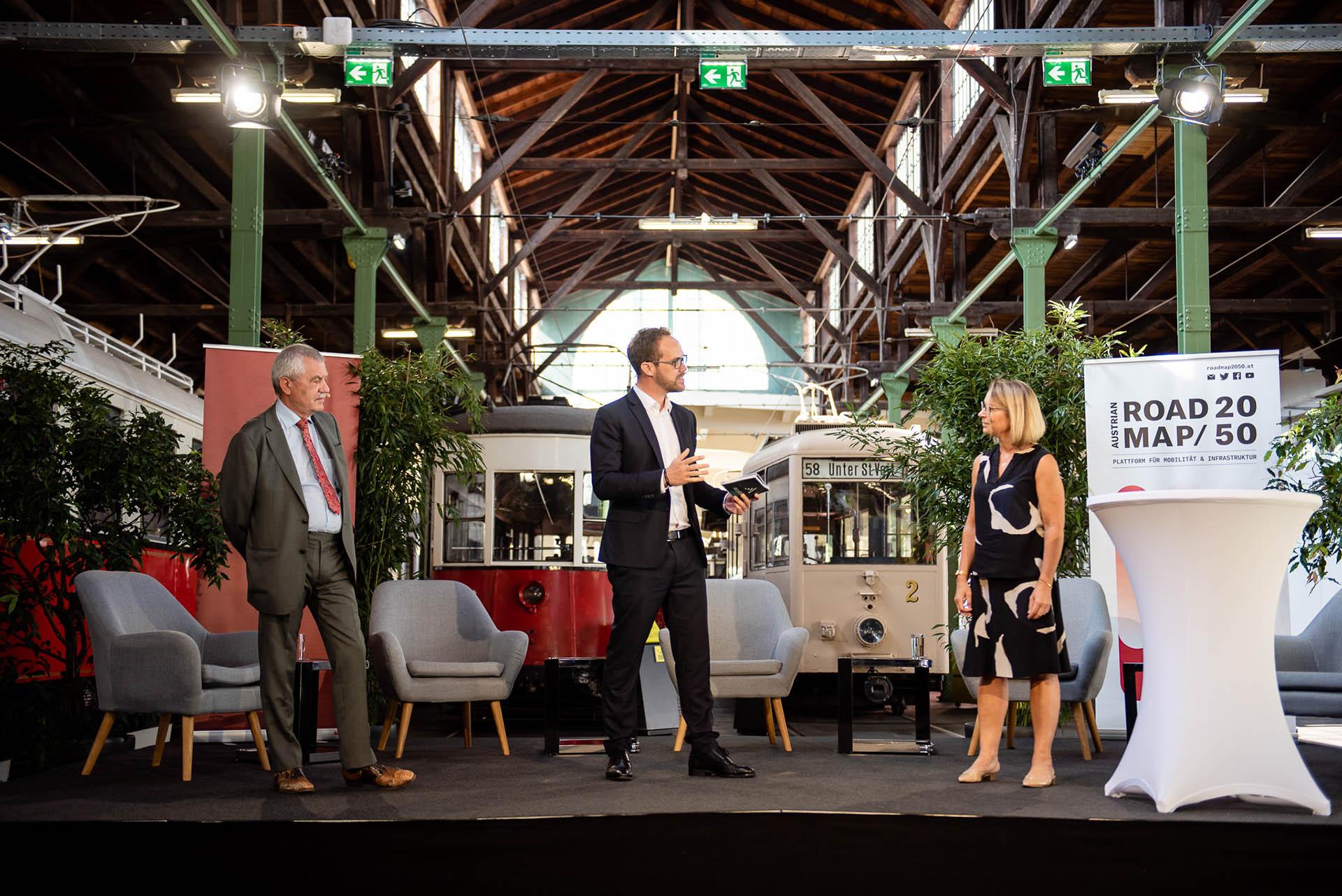 Günter Steinbauer, Alexander Hotowy und Alexandra Reinagl stehen auf einer Bühne bei einer Live-Streaming-Veranstaltung und sprechen miteinander.