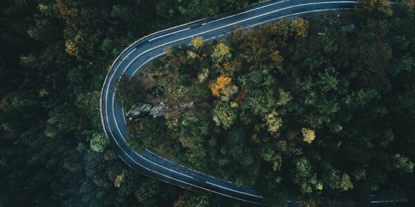 Luftaufnahme einer Straße, die sich im Wald befindet und eine gerade Kurve von 180 Grad beschreibt.