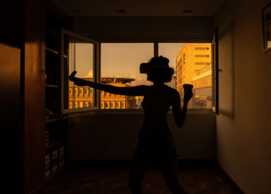 A woman standing in what seems to be here flat wearing a virtual reality device. In the background you can see through a window and get a glimpse of neighbour buildings.