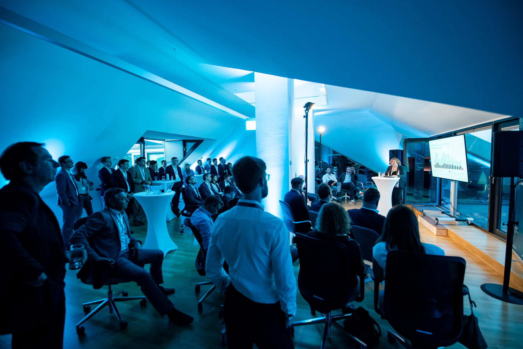 Blue top floor of a building with sloping roofs on the left and right side. At least 40 people are visible. The light is blue and rather dark. On the right side you can see a speaker holding a keynote in front of a screen, on the right side the audience is listening.