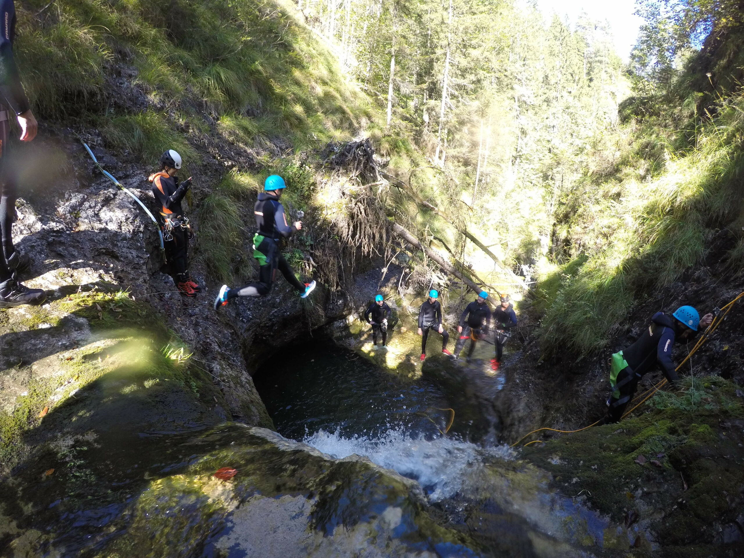 An accilium employee is jumping from a cliff inside a canyon into a big natural pool. Several other accilium employees are standing aside and applaude him.