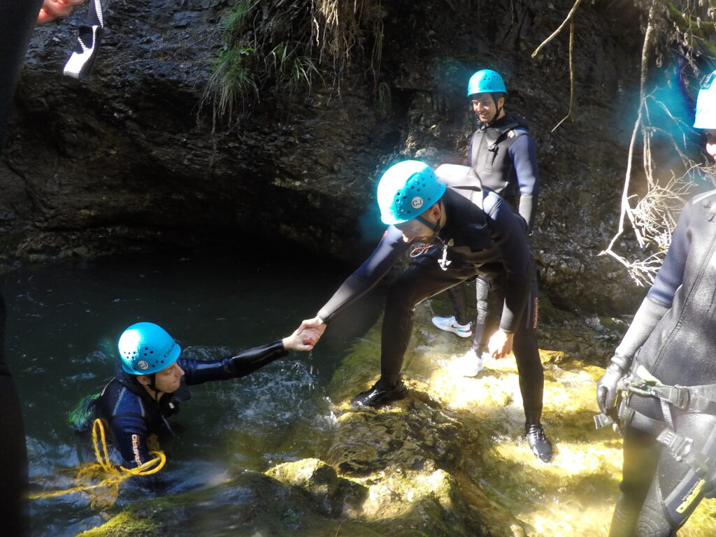 accilium employees in neoprene suits and equipped with climbing gear and helmets wandering through a guided canyoning tour in a mountain stream