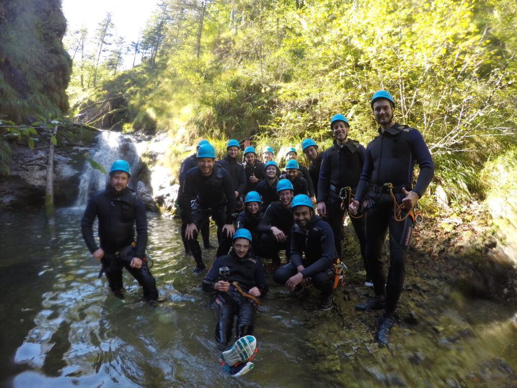 16 accilium employees in neoprene suits and equipped with climbing gear and helmets are standing inside a canyon.