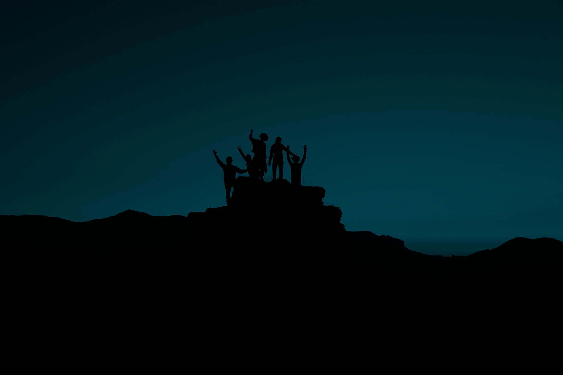 A group of people standing on a hill, that look like they are celebrating.