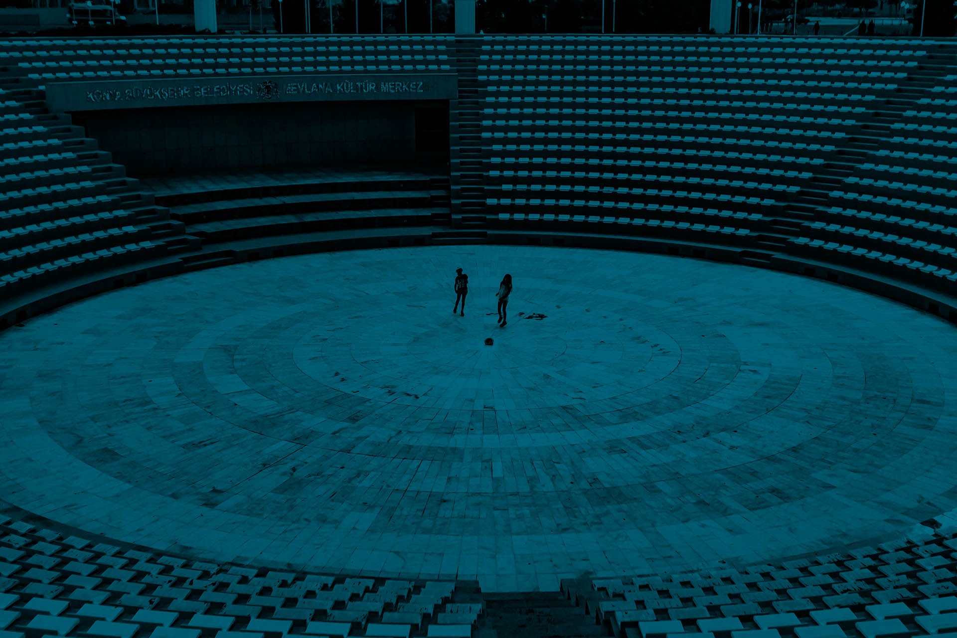 Two children standing in the center of a a round colloseum-like stage in front of empty seats.