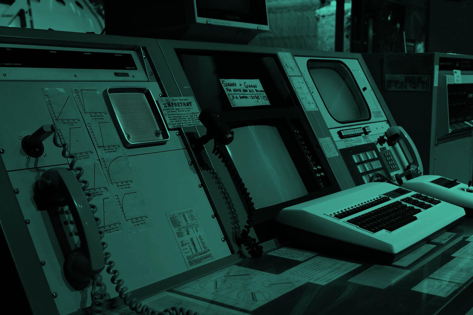 Eine ziemlich alte Kommandozentrale mit verschiedenen Bildschirmen und einem Oldschool-Telefon.