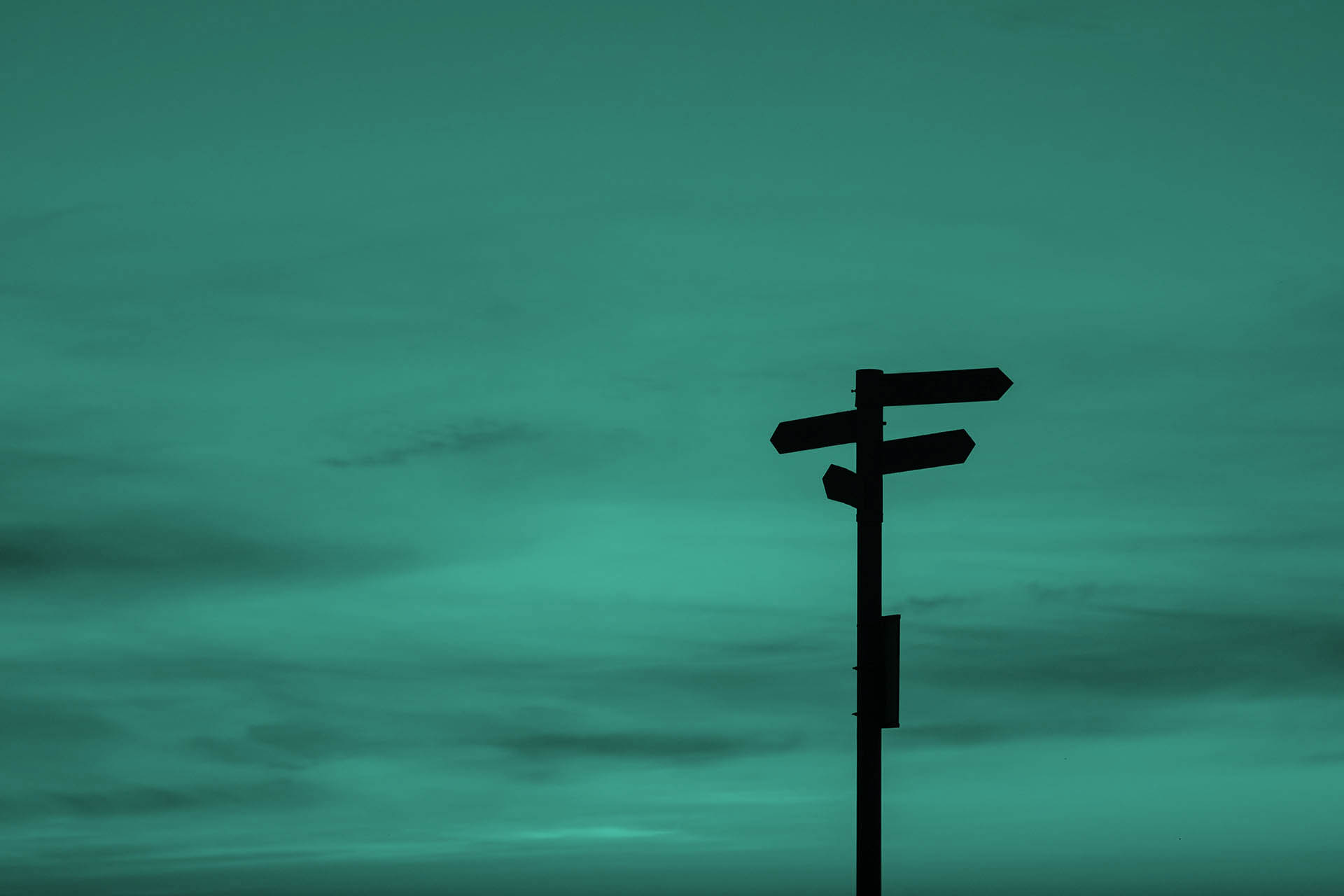 Directional signs, which can only be recognised as black outlines due to the contrast and incidence of light, stand in front of a bluish-red horizon with individual clouds.