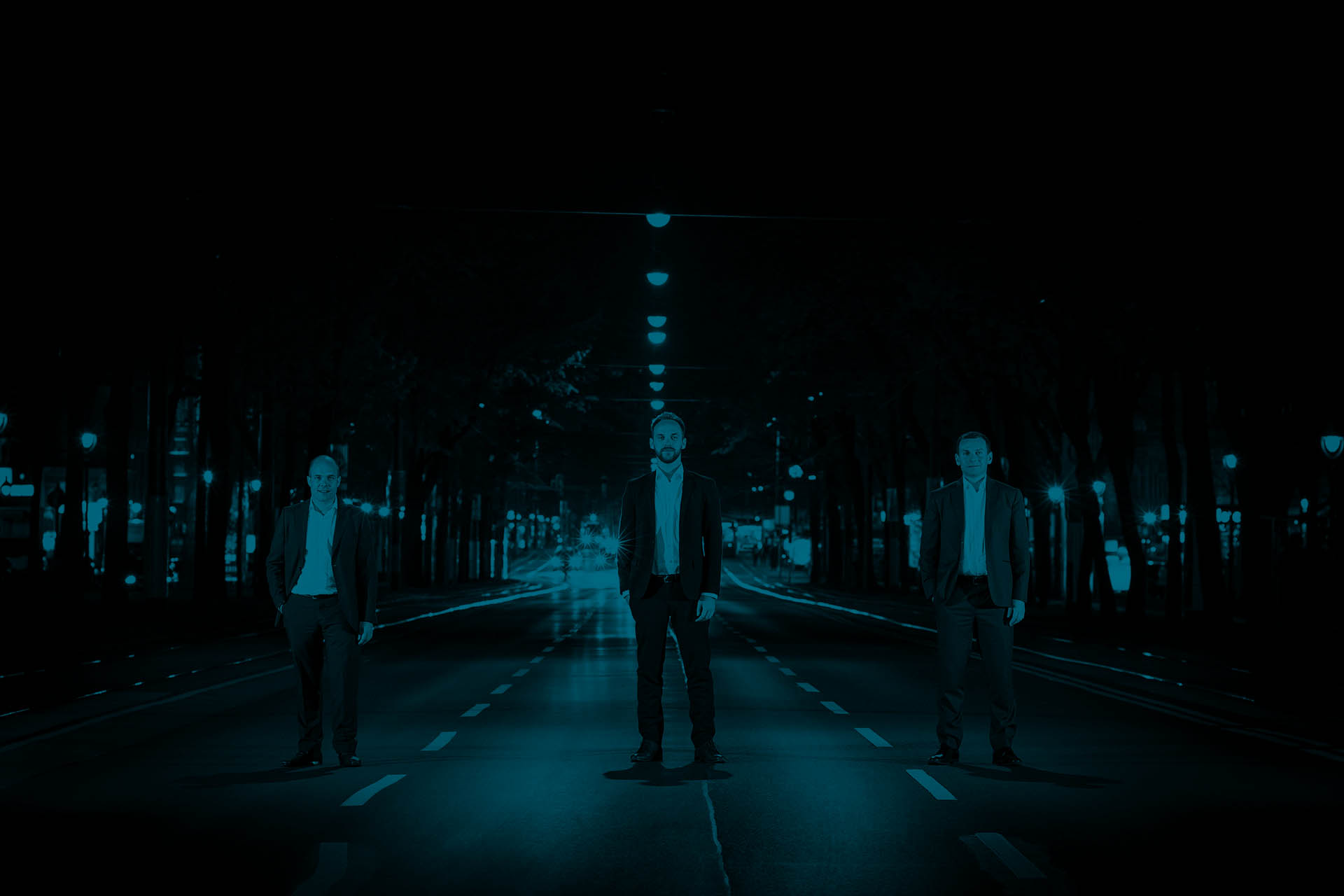 The three managing partner of accilium are standing on a three lane road looking towards the camera. Behind them there are cars approaching them. Its dark in the evening.