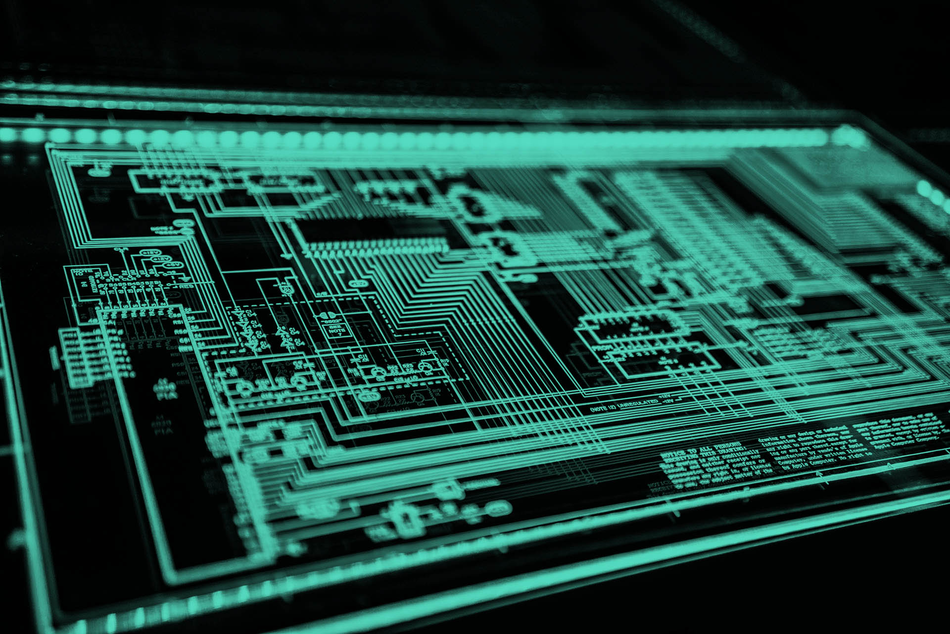 Something that looks like a computer motherboard with chips and wires glows green. The rest of the picture is black.