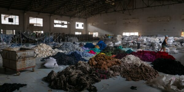 A huge industrial hall with many piles of textile garbage in different colours on the floor. Two women carrying some textiles from the center to the right.